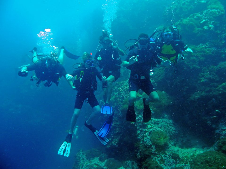 Family scuba diving at Sail Rock i the Gulf of Thailand